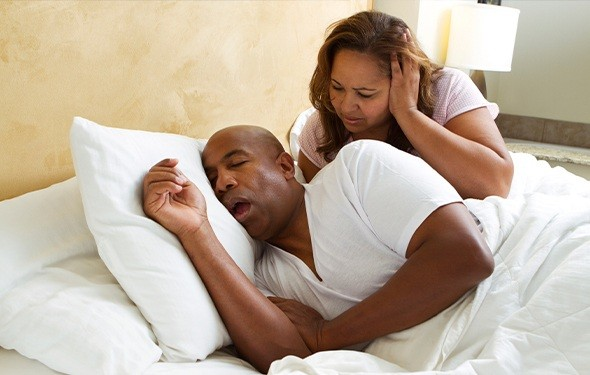 Frustrated woman in bed with snoring man